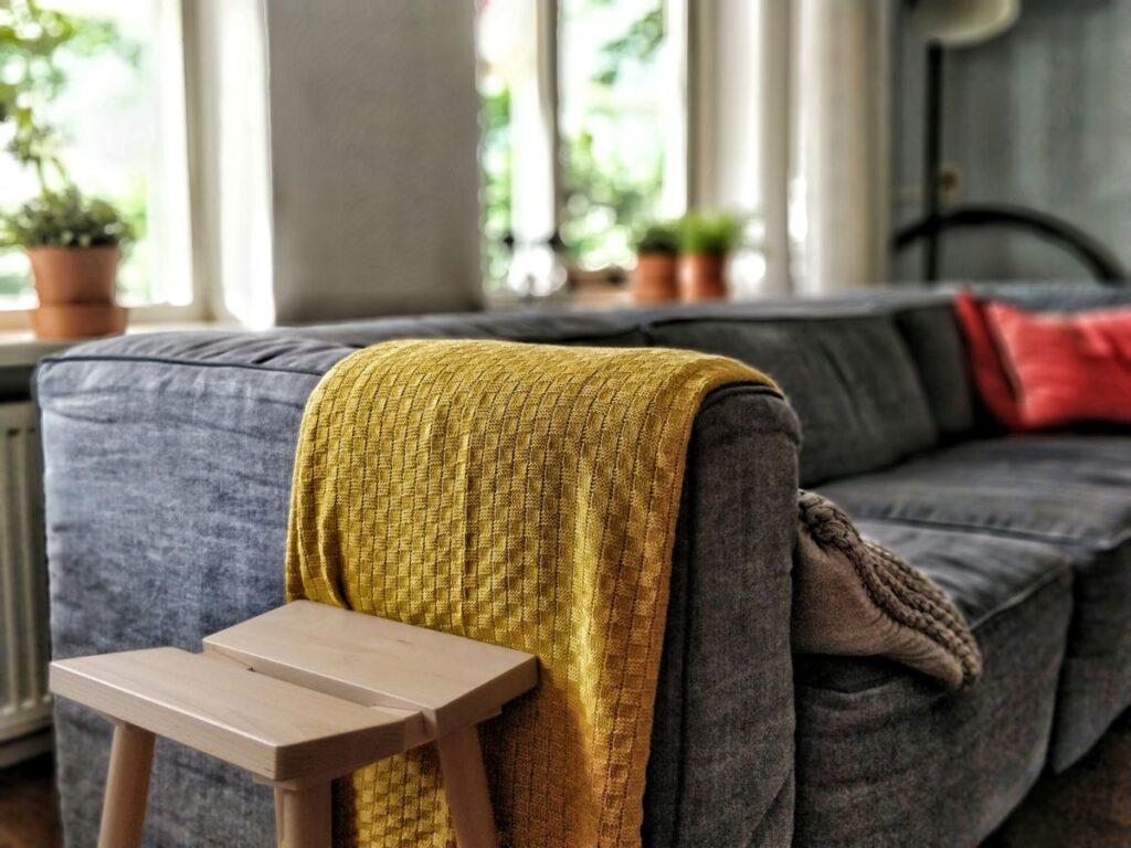 Grå sofa med gult teppe og rød pute